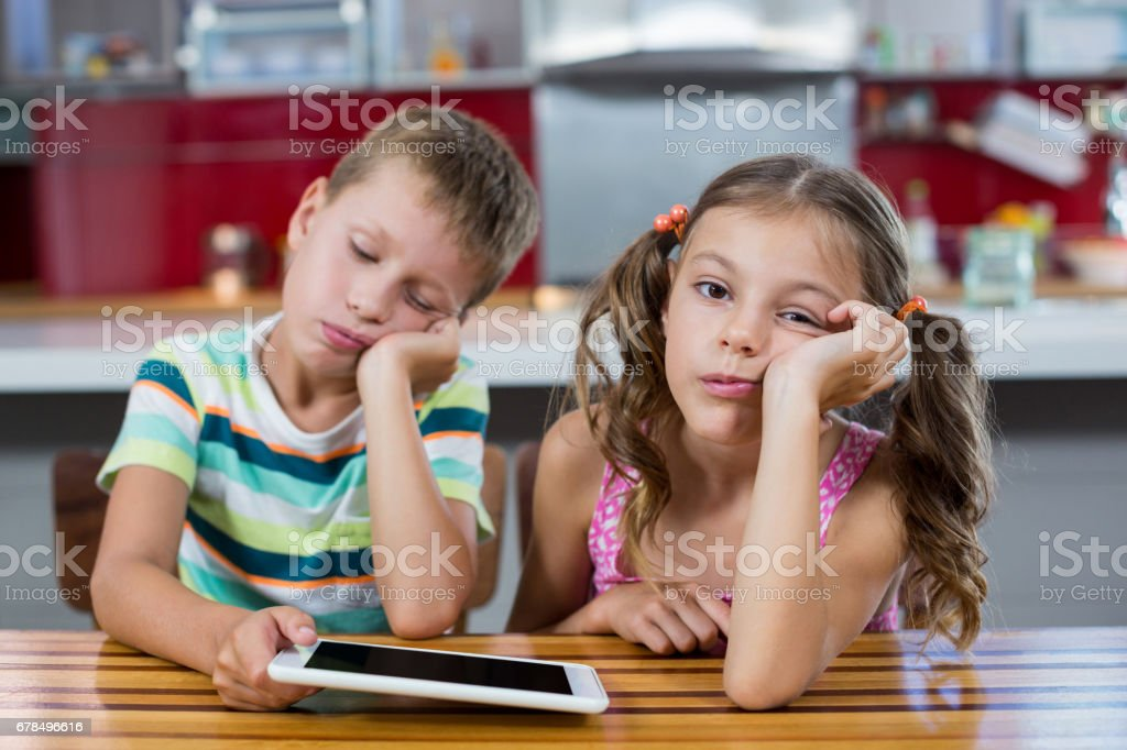 Bored siblings with digital tablet in kitchen stock photo