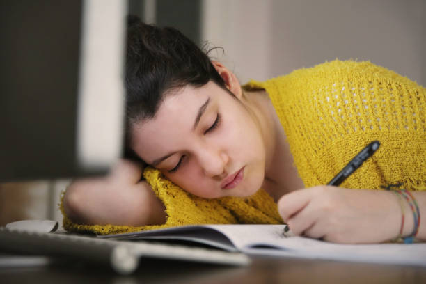 Bored student looking desktop pc in coronavirus confinement stock photo