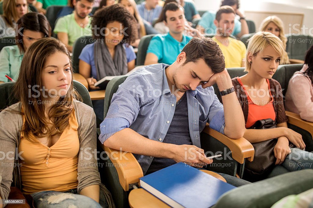 Bored student text messaging on cell phone during a lecture. stock photo