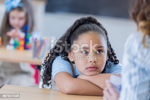 istock Bored student uses flashcards in class 667947048