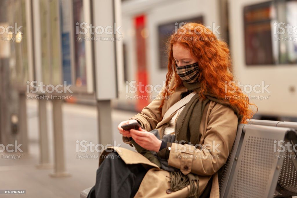 Bored teen student wearing a face mask checks her mobile phone while waiting for her commuter train to arrive Female student with long curly red hair wearing a protective facial mask, in the city railway station. Spends time on her phone while waiting for her train to arrive. Dressed in stylish coat with matching scarf. 18-19 Years Stock Photo