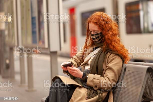 Bored Teen Student Wearing A Face Mask Checks Her Mobile Phone While Waiting For Her Commuter Train To Arrive Stock Photo - Download Image Now