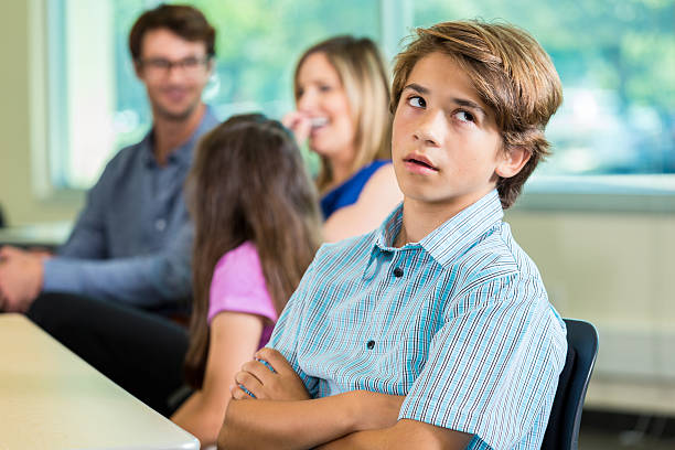 Bored teenage boy during parent teacher conference stock photo