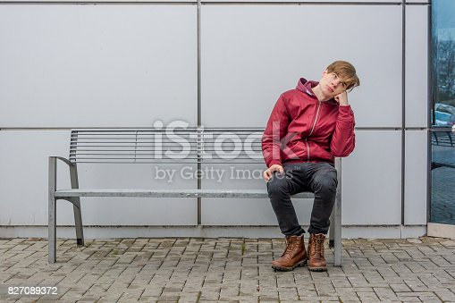 Bored teen waiting for parents outdoor on the metal bench in front of shopping center in city sitting alone thinking and hoping expressing dissatisfied emotions