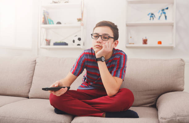 bored teenage boy watching tv at home - laziness stock photos and pictures