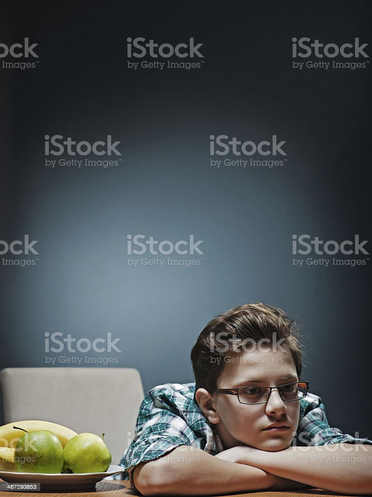 Bored teenager refusing to eat fruits. stock photo