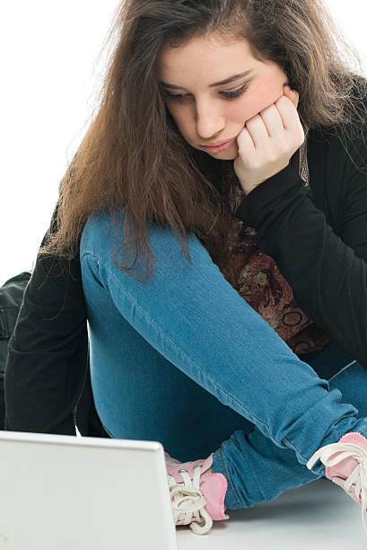 Entediado adolescente usando laptop - foto de acervo