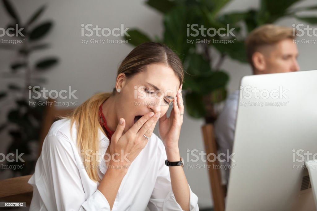 Bored tired businesswoman yawning at workplace feeling lack of sleep stock photo