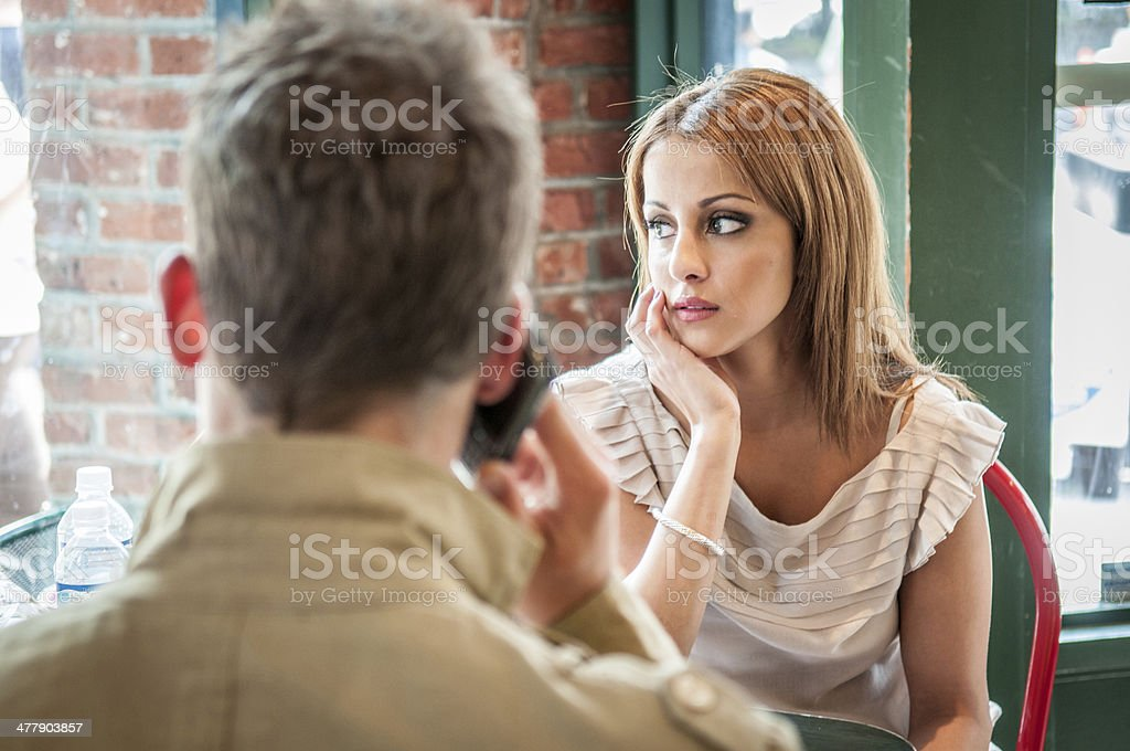 Bored when boyfriends using mobile phone during a date stock photo