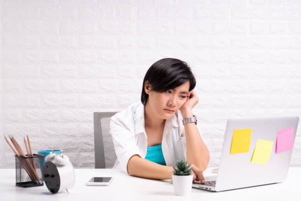 Bored woman at office working with a laptop stock photo
