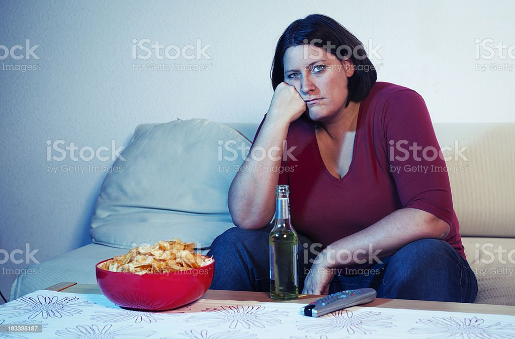 Bored woman in front of tv stock photo