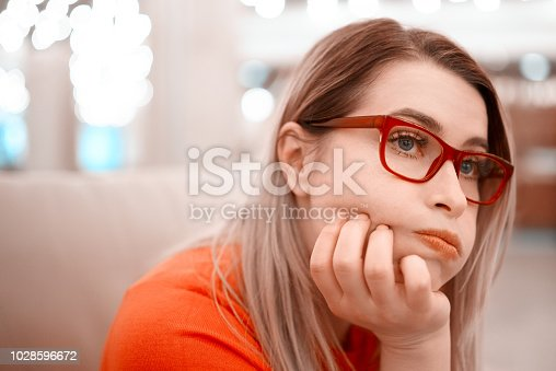 lifestyle shot of bored woman indoors, holding head and looking away.