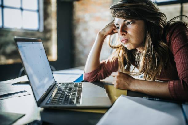 Sıkılmış kadın bilgisayar dan e-posta okuyor. stok fotoğrafı