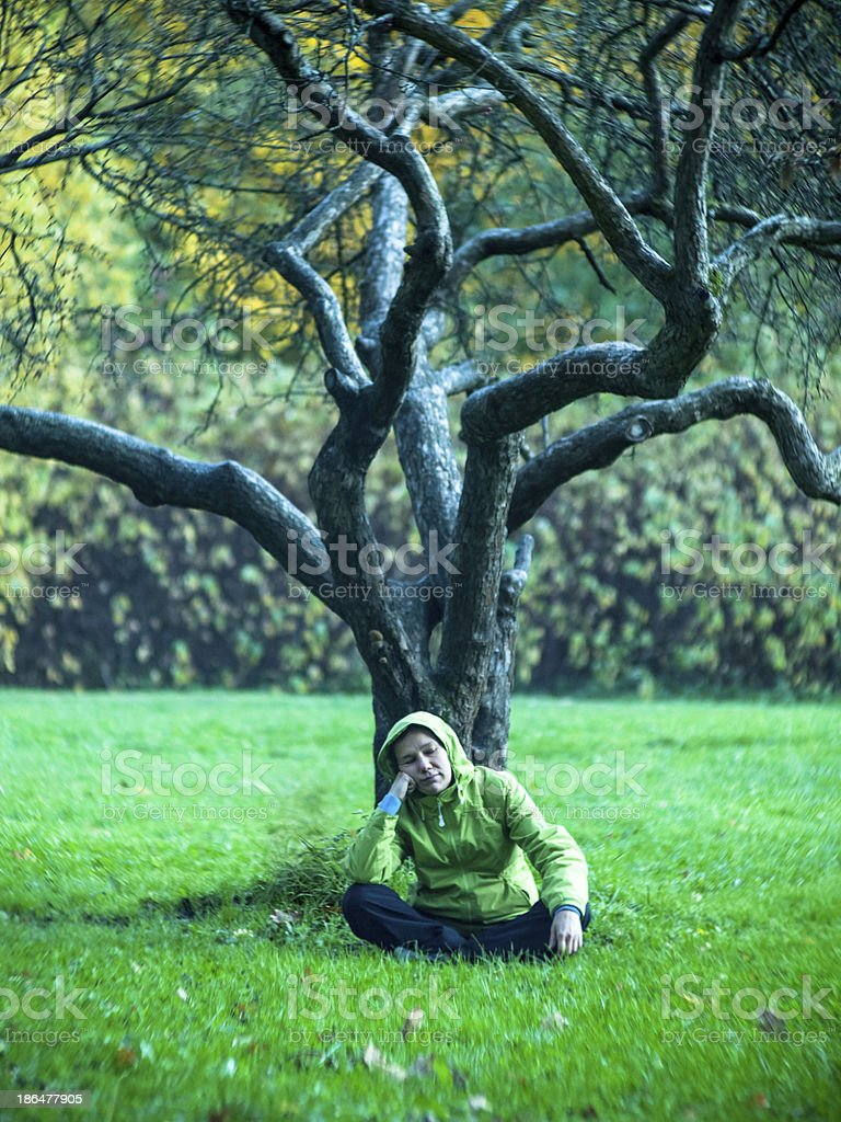Bored woman sitting on the grass royalty-free stock photo