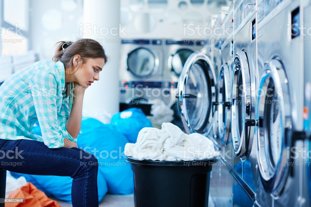 Bored woman sitting opposite to washing machines stock photo