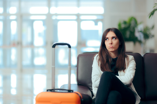 Bored Woman with Suitcase in Airport Waiting Room