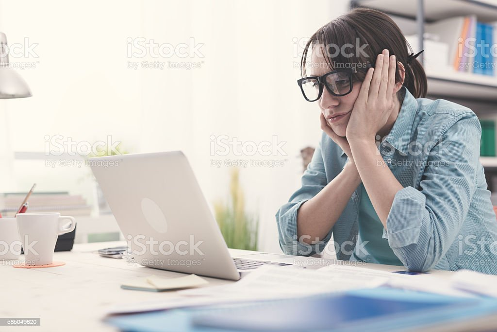 Bored woman working with her laptop stock photo
