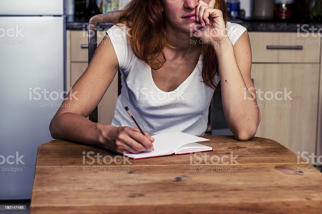 Bored woman writing in her kitchen royalty-free stock photo
