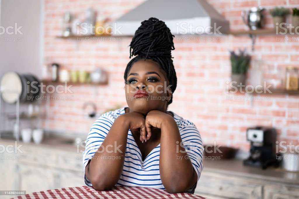 Young african woman sitting home alone, bored.