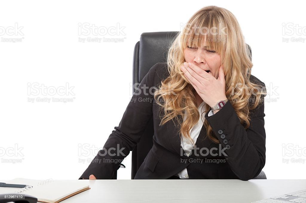 Bored young businesswoman yawning stock photo