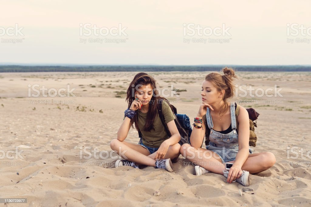 Bored young friends sitting on sand in desert Bored young friends sitting on sand. Beautiful females are lost in desert during hiking. Hipsters are wearing casuals. 20-24 Years Stock Photo