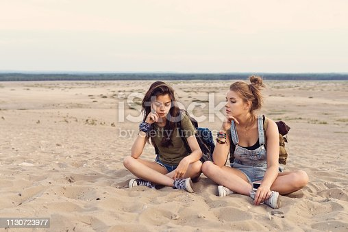 Bored young friends sitting on sand. Beautiful females are lost in desert during hiking. Hipsters are wearing casuals.