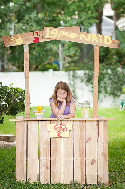 Bored young girl with no customers at her lemonade stand stock photo