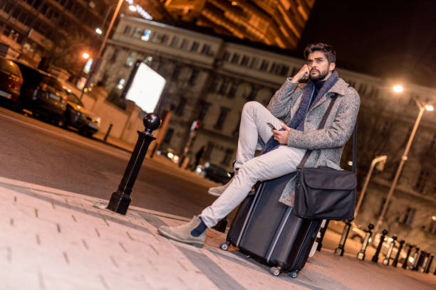 Bored young man on business travel waiting for taxi on city street. stock photo