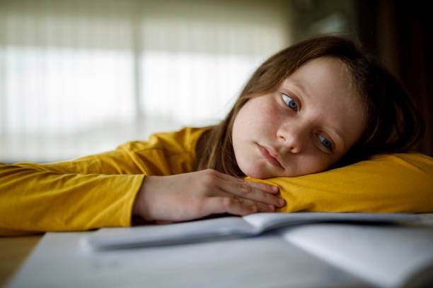 Bored young school girl studying at home stock photo