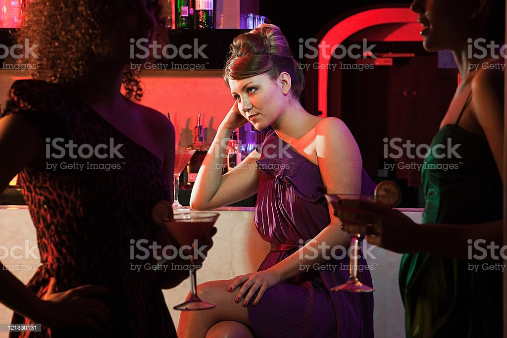 Bored young woman sitting at cocktail bar stock photo