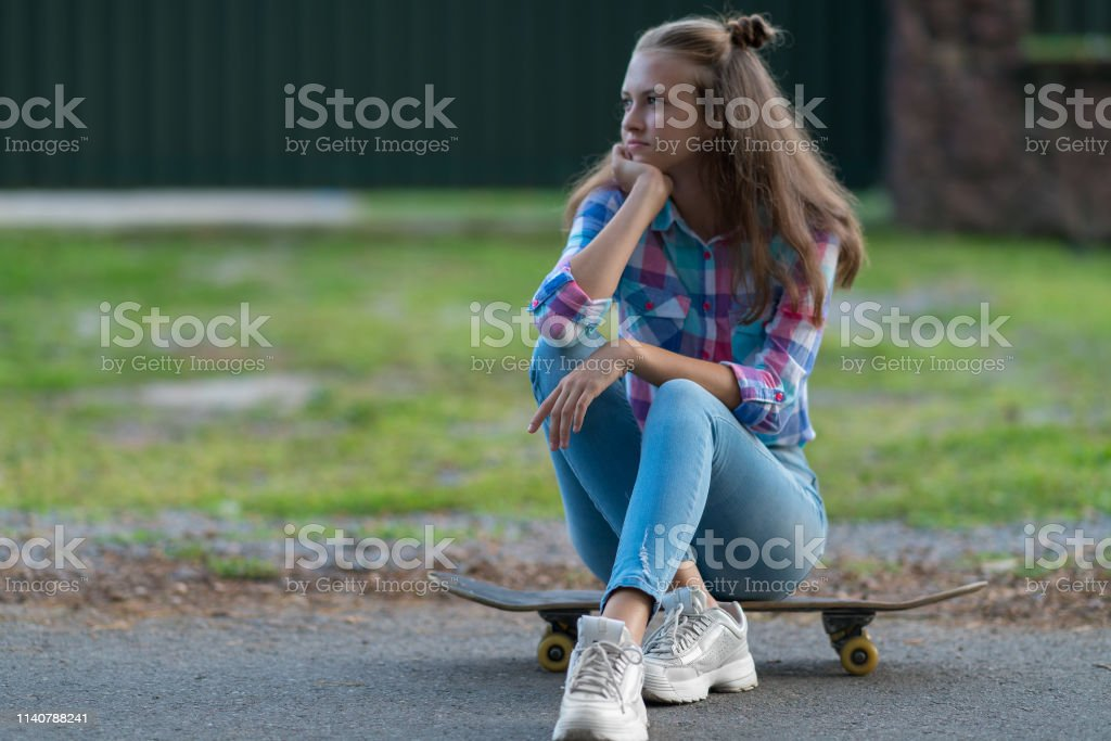 Bored young woman sitting waiting on a skateboard watching for...