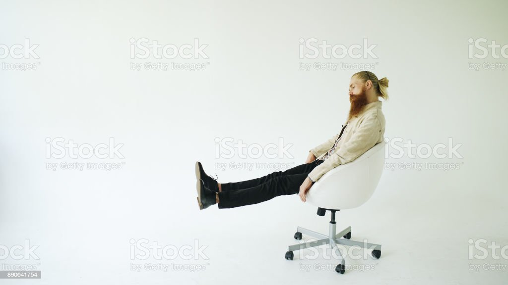 Boring bearded man turning on swivel office chair on white background stock photo