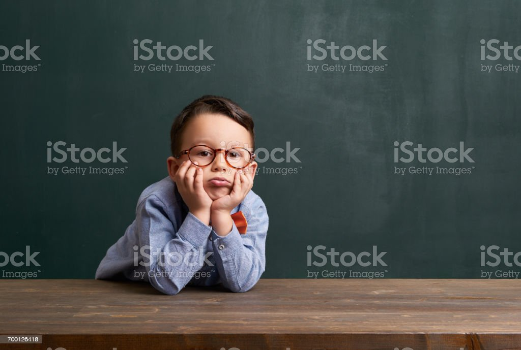 Boring child is in front of chalkboard