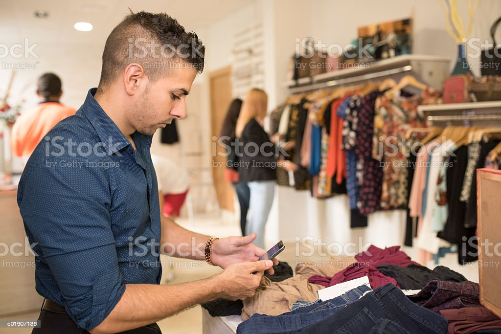 Boring man looking phone while his girlfriends shopping stock photo