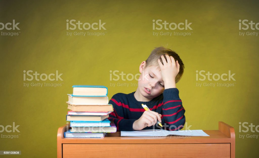 Boring School Studies. Homework. Tired little boy writing. Education concept. stock photo