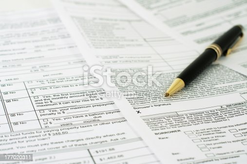 Loan papers are spread out and a pen points to where the borrower signs
