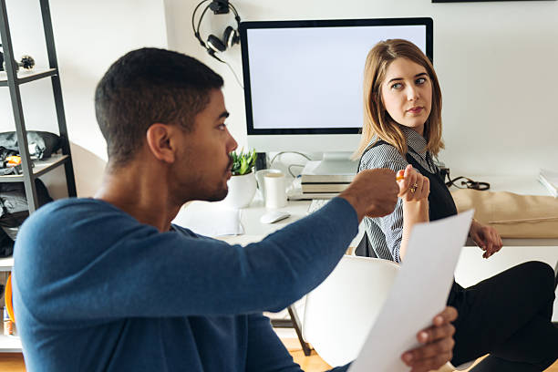 Borrowing a pen Shot of a man borrowing a pen to his coworker. borrowing stock pictures, royalty-free photos & images