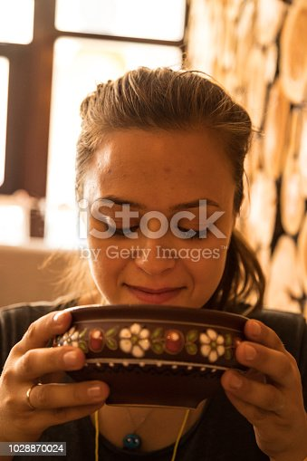 Borsh. Russian and Ukrainian traditional vegetarian red soup. Woman drinking soup.