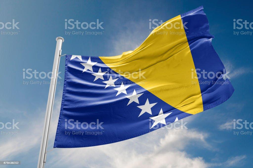 Bosna-Hersek bayrağı sallayarak karşı mavi gökyüzü olduğunu stok fotoğrafı