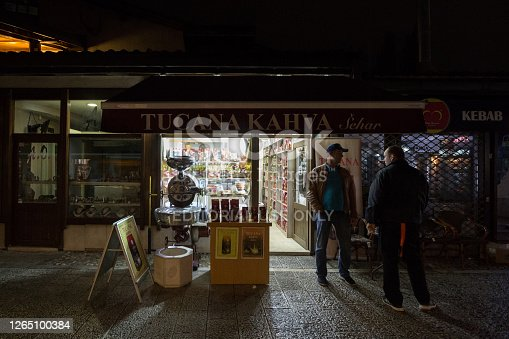 Picture of a boutique selling Bosnian coffee with coffee packs ready to be sold next to a grinder and people discussing next to it. Close to Turkish coffee, Bosnian coffee is a typical drink from Bosnia and from Sarajevo.