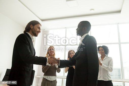 923041456 istock photo Boss and team appreciating black businessman by handshake and applause 958531460