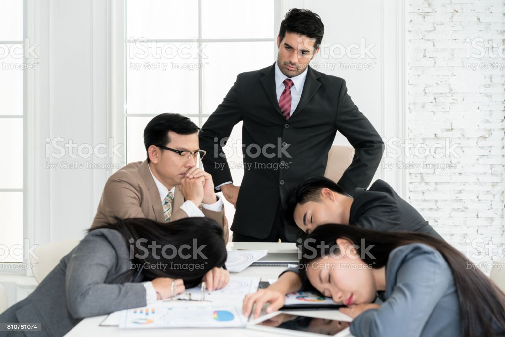 Boss angry when business people team sleeping on meeting room in office. Business people team tired after working hard. stock photo