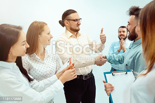 815703312 istock photo Boss approving and congratulating young successful employee 1131170565
