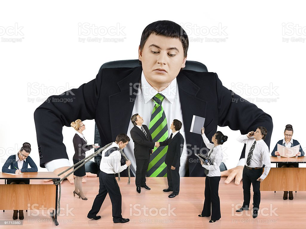 Boss at a desk looking down at a miniature business team royalty-free stock photo