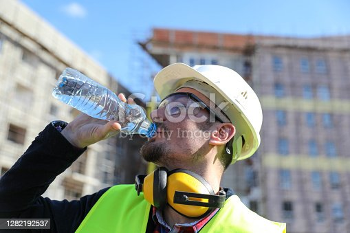 istock boss at construction site with bottle of water, close up 1282192537