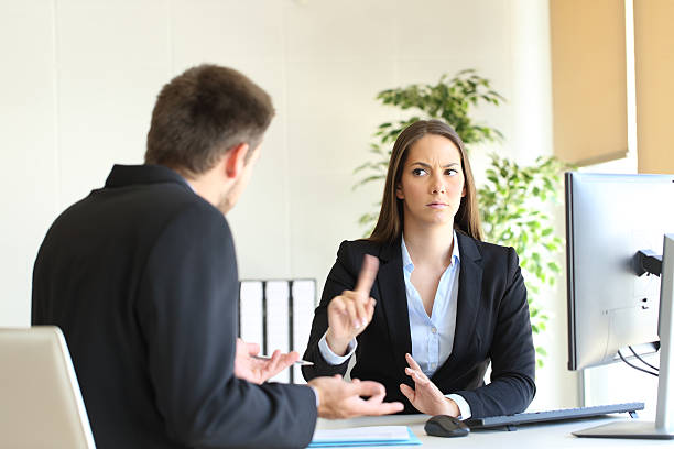 Boss denying something to an employee Boss denying something saying no with a finger gesture to an upset employee in her office negative emotion stock pictures, royalty-free photos & images
