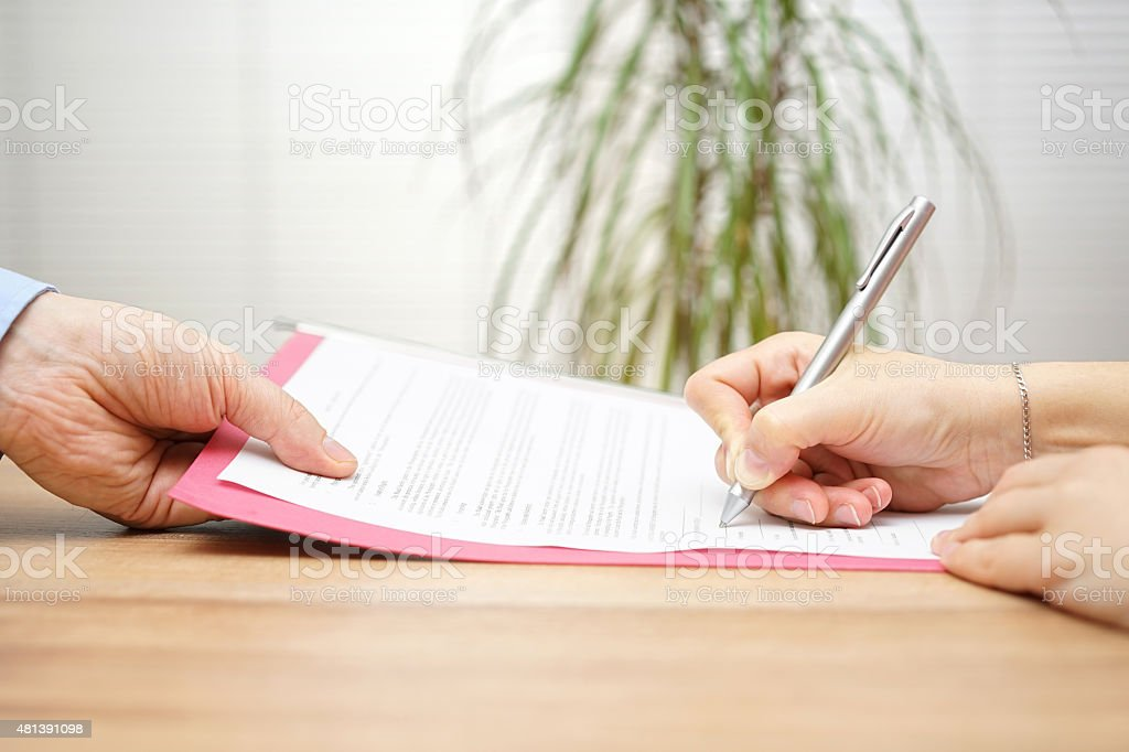 boss gives employee dismissal contract to sign stock photo