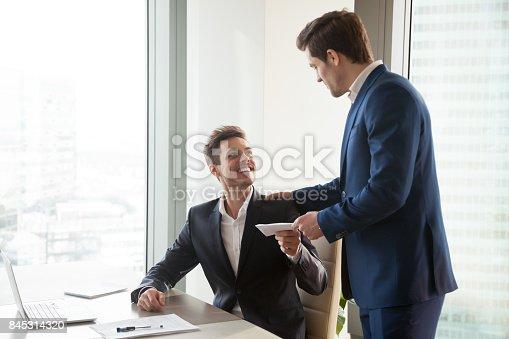 1018458132istockphoto Boss giving money premium to happy employee 845314320