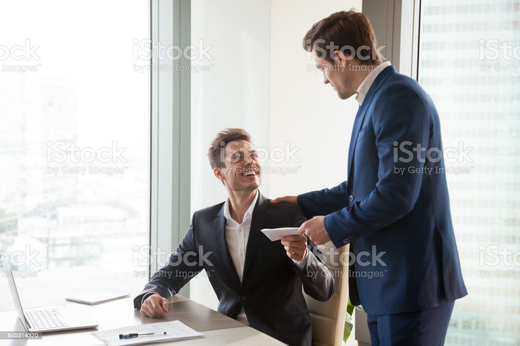 Chefe dando prêmio de dinheiro ao funcionário feliz - foto de acervo