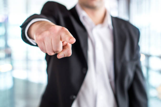 Boss giving order or firing employee. Powerful business man pointing camera with finger. Angry executive or manager. stock photo